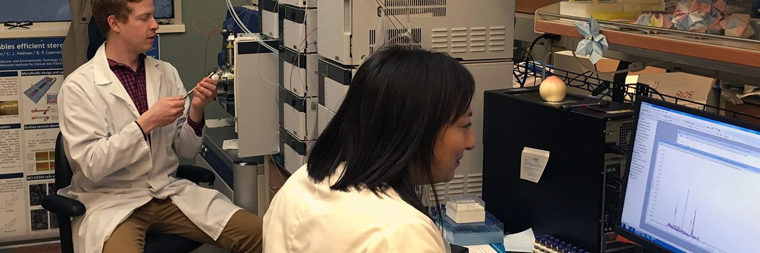 Assay Services staff member Robin Goy loads a sample on the LC/MS/MS while Amita Kapoor studies Vitamin D data generated on the instrument.