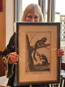 Toni holding a vintage framed marmoset print, a gift from Chuck Snowdon